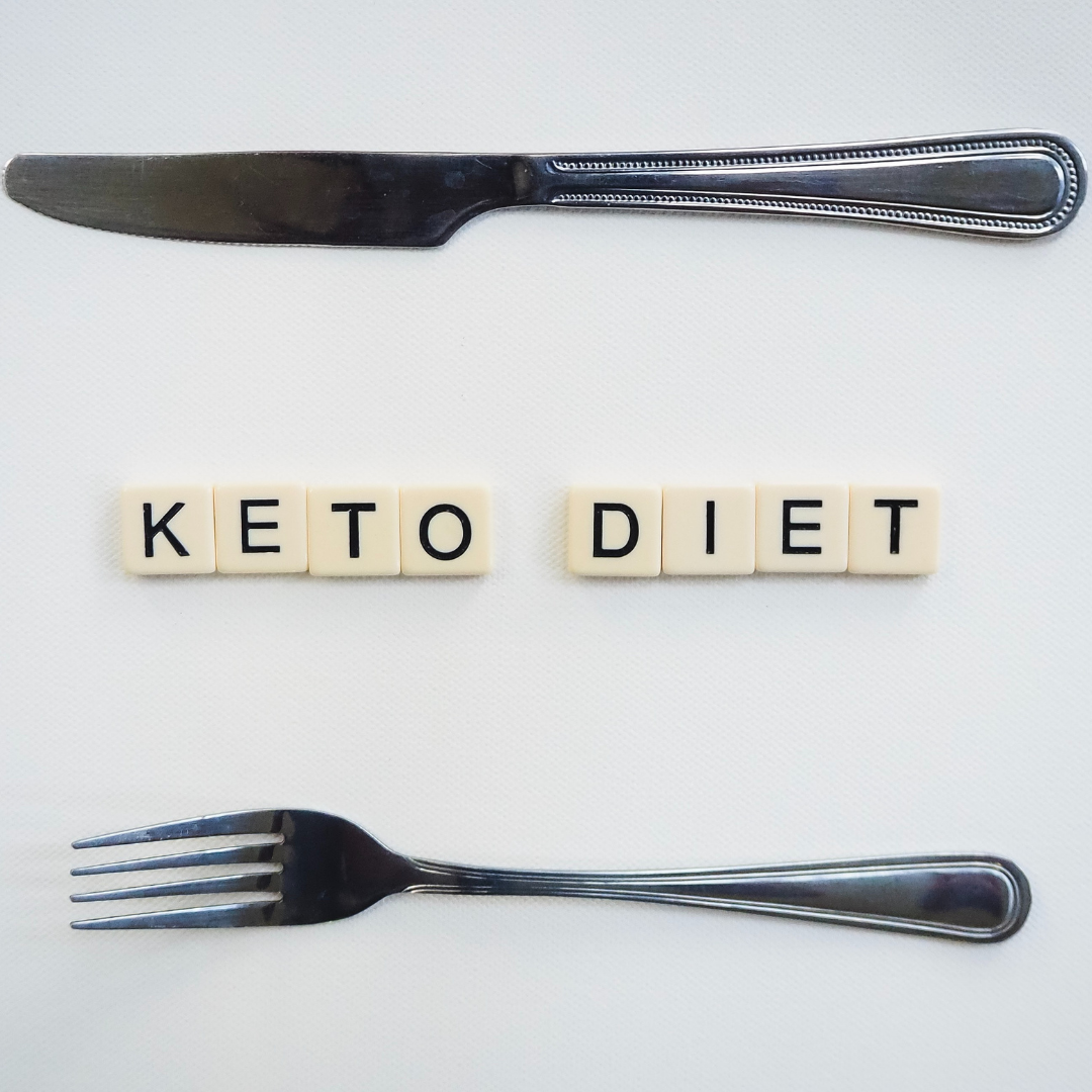 "Imagen en la que se ve en la parte superior un cuchillo, en la inferior un tenedor y en el medio unas fichas con letras en las se puede leer ""KETO DIET"""